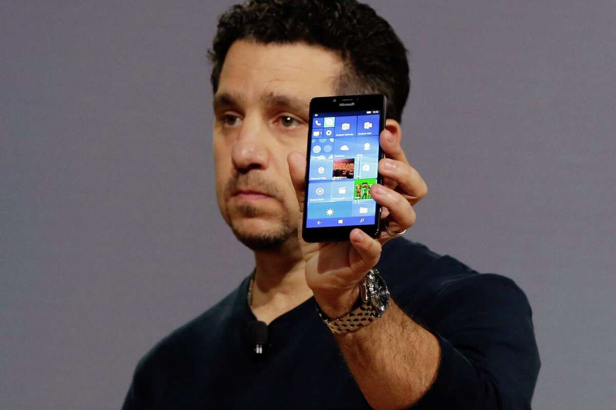 Microsoft vice president for Surface Computing Panos Panay shows a new Lumia 950 phone. The device will work with an optional dock. Users can attach a regular monitor, keyboard and mouse and work with apps on the phone just like you would on a Windows 10 desktop. (AP Photo/Richard Drew)