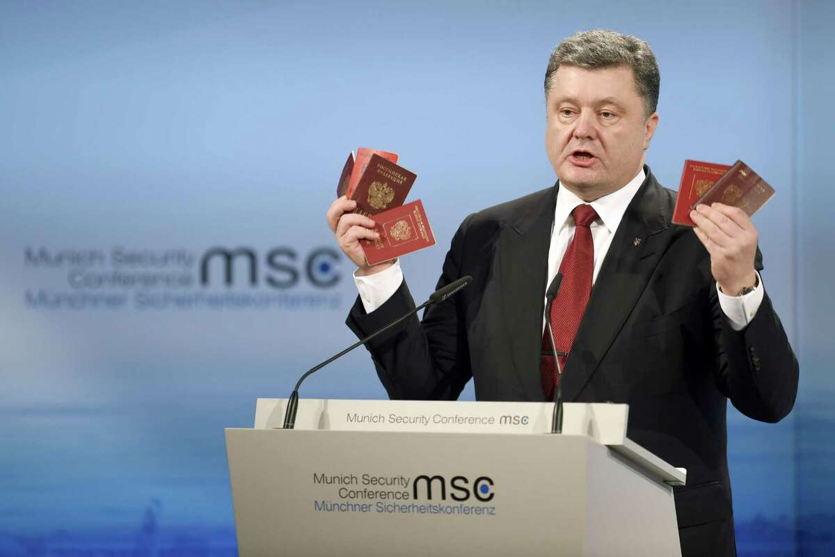 Ukraine's President Petro Poroshenko holds Russian passports claiming they are proof of the presence of Russian troops in Ukraine as he addresses the 51. Security Conference in Munich, Germany, Saturday, Feb. 7, 2015. The conference on security policy takes place from Feb. 6, 2015 until Feb. 8, 2015. (AP Photo/dpa, Tobias Hase)