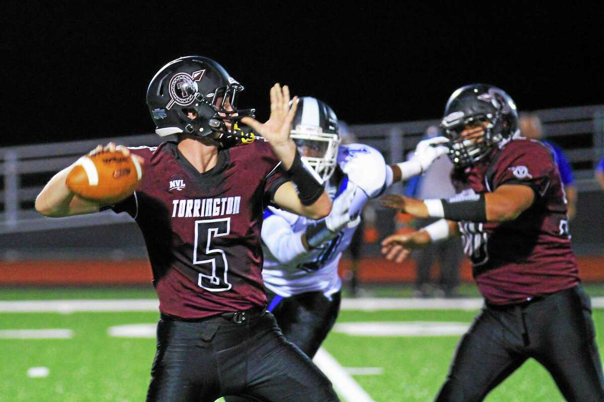 Torrington quarterback Connor Finn stays focused against a Crosby defender in the Red Raiders' first win of the season.