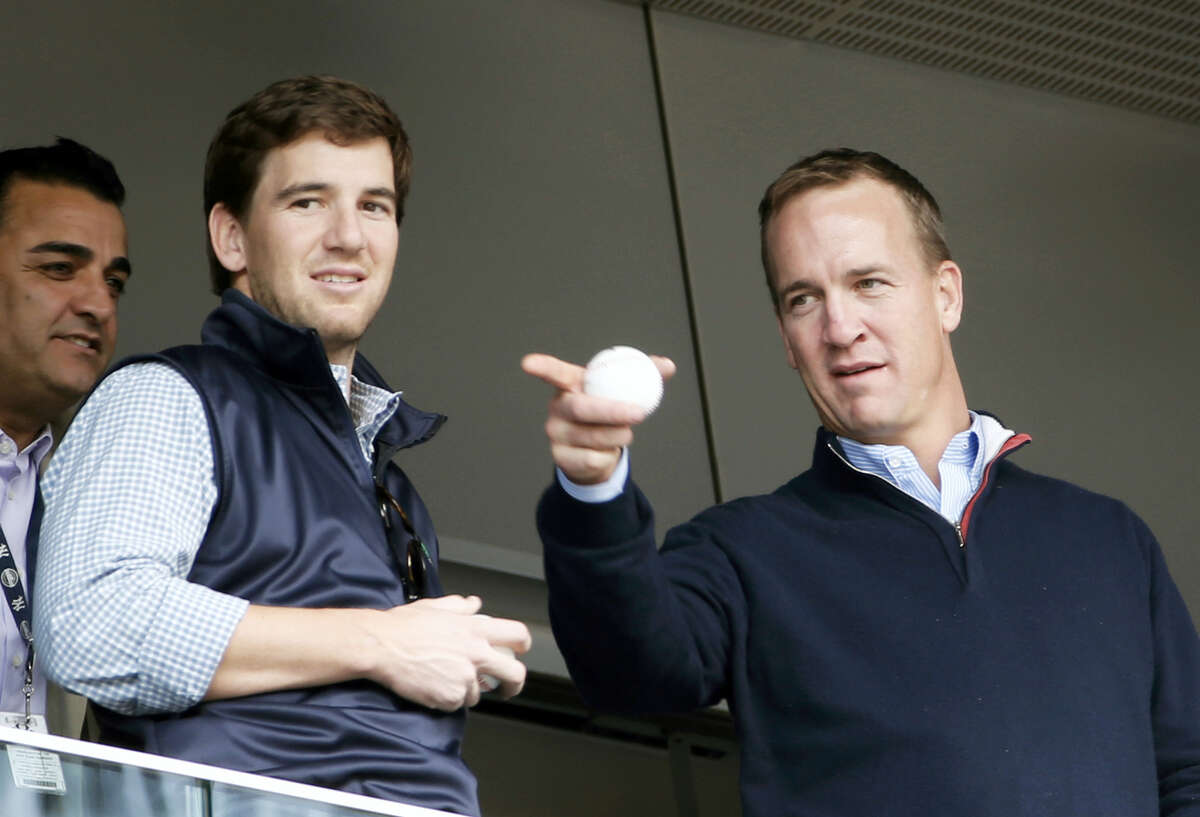 """In this 2014 file photo, Peyton Manning, right, points out something in the stadium to his brother Eli Manning from Yankees' Derek Jeter's suite during a baseball game at Yankee Stadium. Peyton Manning had a little fun with little brother Eli's sad face at the Super Bowl during an appearance on NBC's """"Tonight Show."""""""
