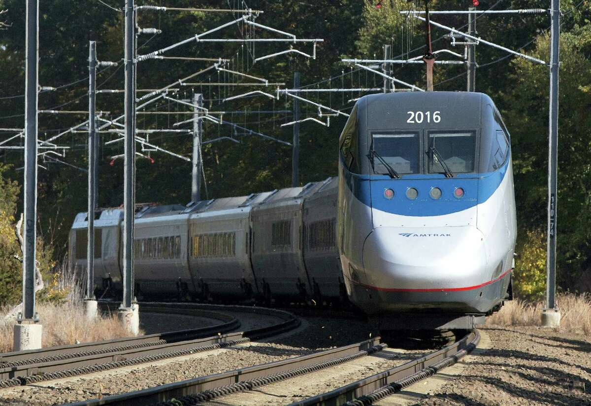 In this Oct. 18, 2016 photo, an Amtrak Acela train travels through Old Lyme, Conn. A plan to speed up Amtrak's high-speed rail corridor from Boston to Washington, D.C., is welcomed by business commuters but finding its strongest opposition in some shoreline towns in Connecticut.