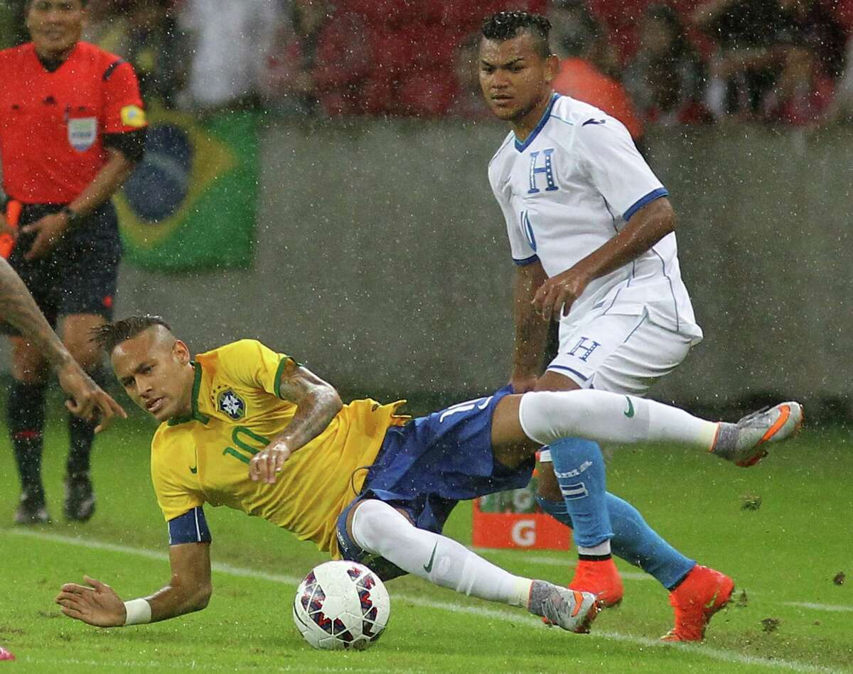 Brazil's Neymar, left, is taken down by Honduras' Mario Martinez during a friendly soccer match in Porto Alegre, Brazil on June 10, 2015. Brazil is preparing for the Copa America which begins Thursday in Chile.