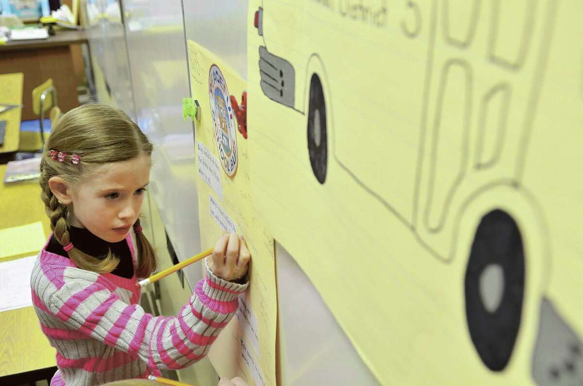Third-grader Kaitlin Hersh signs a pledge with a list of behavior rules for riding a school bus in this 2012 file photo.
