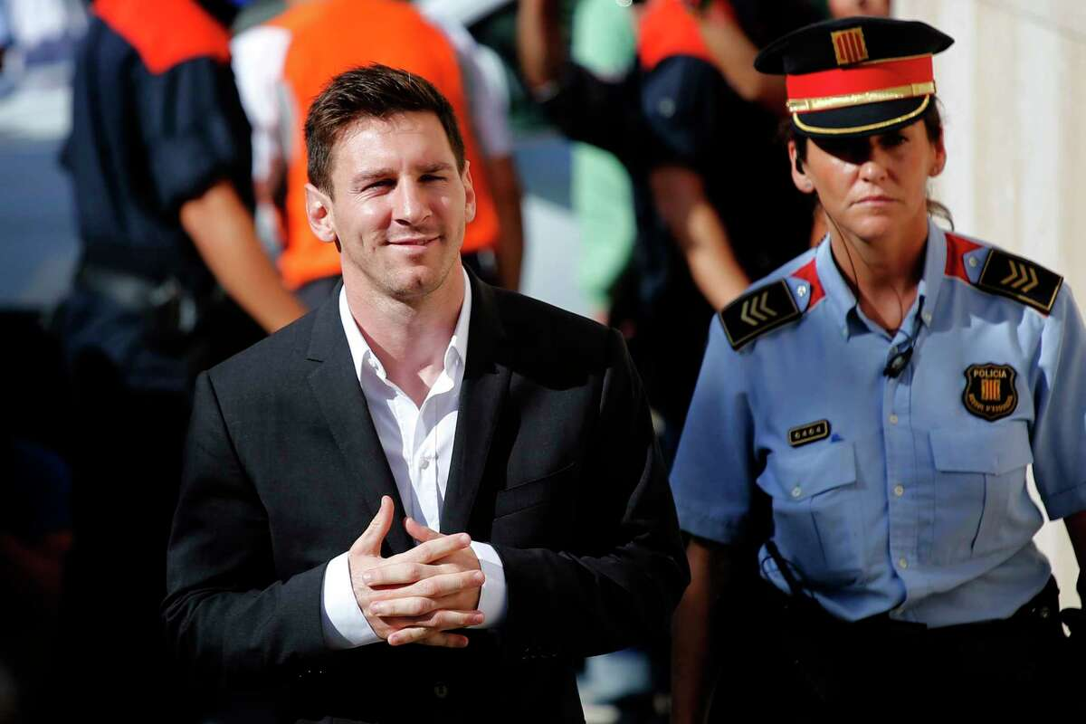 In this Sept. 27, 2013 file photo, FC Barcelona star Lionel Messi, left, arrives at a court to answer questions in a tax fraud case in Gava, near Barcelona, Spain.