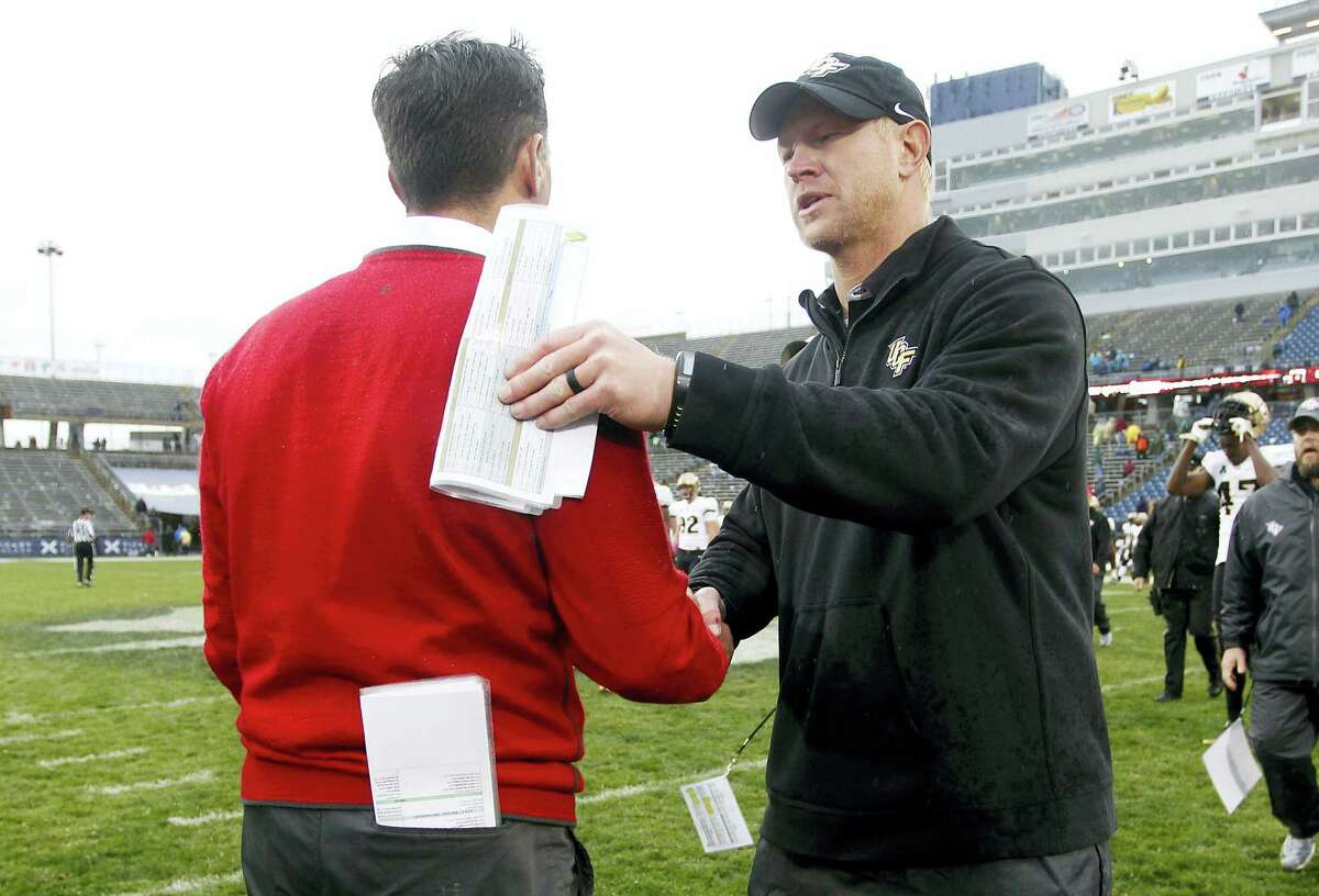 Central Florida head coach Scott Frost, right, shakes hands with UConn head coach Bob Diaco following Central Florida's victory last Saturday at Rentschler Field,