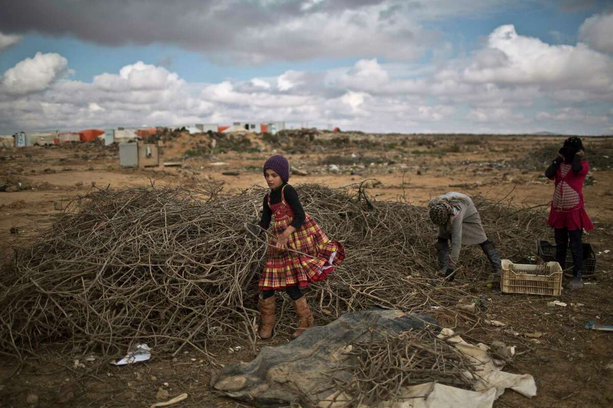 In this file photo, Syrian refugee girls collect wood to be used for heating at an informal tented settlement near the Syrian border on the outskirts of Mafraq, Jordan, Saturday, Jan. 23, 2016. A suicide bomber killed six Jordanian security troops on that border Tuesday, June 21, 2016, and wounded 14 people.