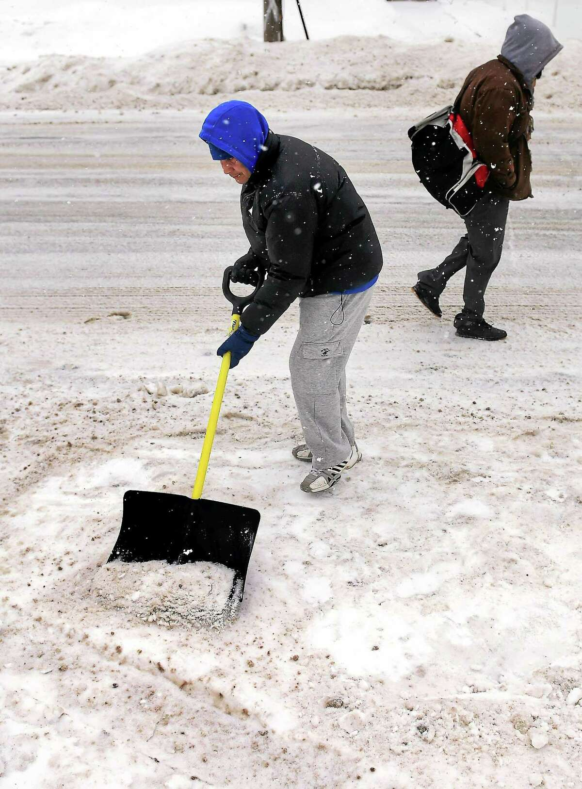 Victor Erazo shovels snow and ice in front of his home on Wakelee Ave. in Ansonia on 2/9/2015.