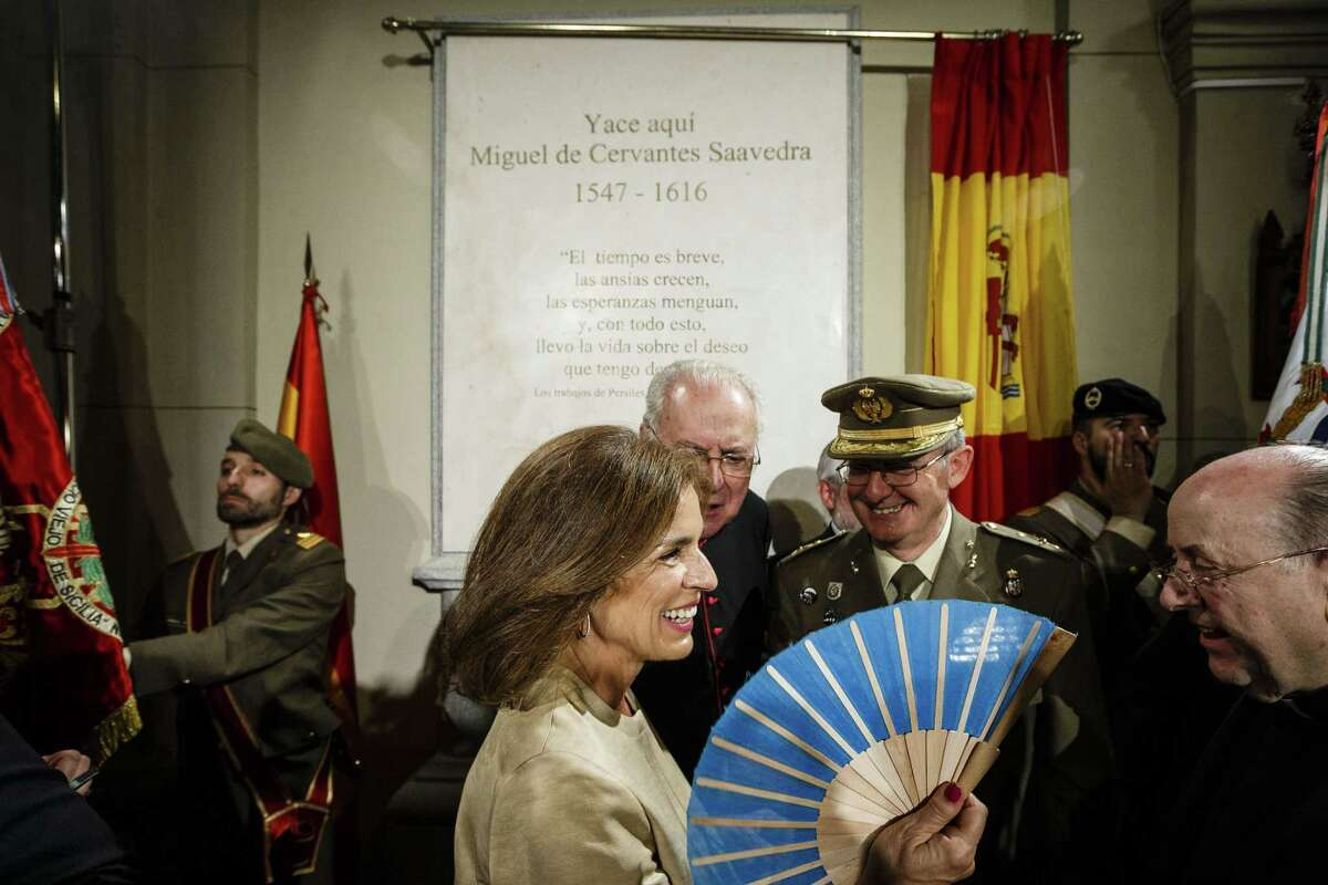 Madrid Mayor Ana Botella, center, uses a fan as she smiles and talks with authorities after a ceremony unveiling a funeral monument holding bone remains believed to include those of Spanish writer Miguel de Cervantes in a Madrid convent, Spain, Thursday, June 11, 2015. Spain has given its greatest writer and author of Don Quixote, Miguel de Cervantes, formal burial some 400 hundred years after his death and after the bones were unearthed this year by experts after a near year-long search at the convent where Cervantes was known to have been buried in 1616. (AP Photo/Daniel Ochoa de Olza)
