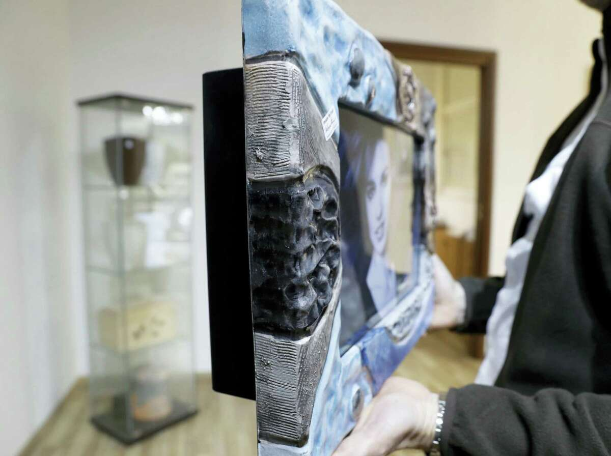 A man holds an urn in the shape of a picture frame at a funeral parlor in Rome, Tuesday, Oct. 25, 2016. The Vatican on Tuesday published guidelines for Catholics who want to be cremated, saying their remains cannot be scattered, divvied up or kept at home but rather stored in a sacred, church-approved place.
