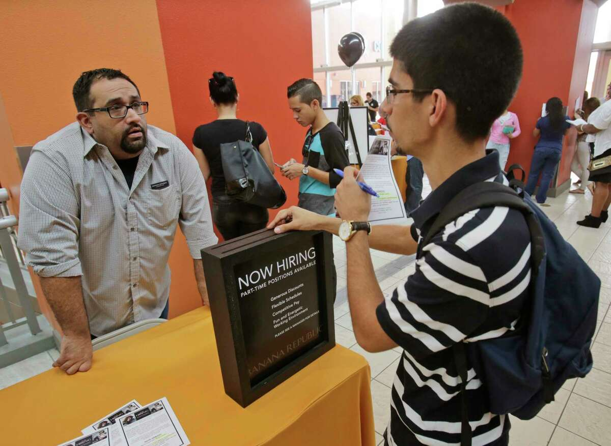 In this Tuesday, Oct. 6, 2015, photo, job applicant Lazaro Fonte, right, 24, of Miami, talks with Banana Republic assistant manager Edward Ortega, during a job fair at Dolphin Mall in Miami. The U.S. Labor Department reports on the number of people who applied for unemployment benefits during the week ending Oct. 3 on Thursday, Oct. 8, 2015.