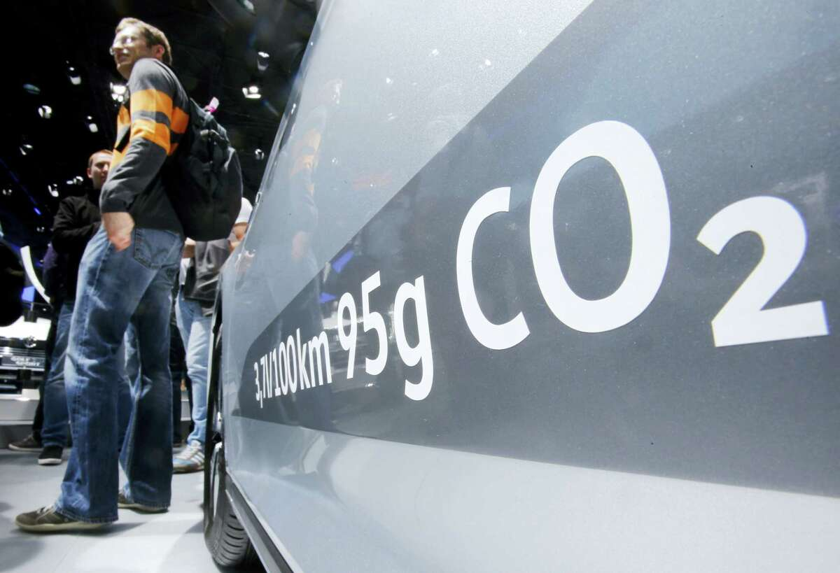 In this Sept. 22, 2015, file photo, the amount of carbon dioxide emissions is written on a Volkswagen Passat Diesel at the Frankfurt Car Show in Frankfurt, Germany. A federal judge in San Francisco has decided to approve a nearly $15 billion deal over Volkswagen's emissions cheating scandal that gives most affected car owners the option of having the company buy back their vehicles. U.S. District Judge Charles Breyer had said last week that he was strongly inclined to give the deal final approval and would issue a ruling by Tuesday, Oct. 25, 2016.