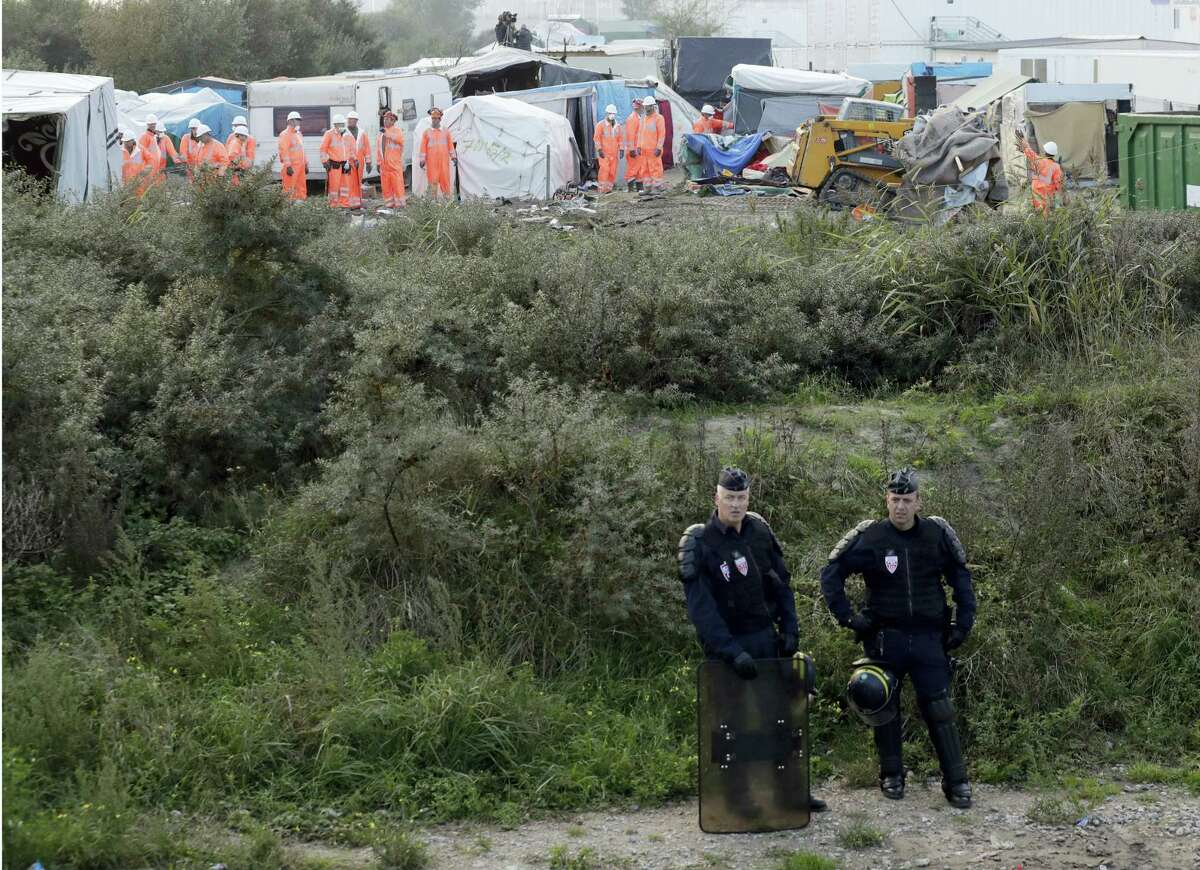 """Riot police take position while crews start to demolish shelters, background, in the makeshift migrant camp known as """"the jungle"""" near Calais, northern France, Tuesday, Oct. 25, 2016. Crews in hard hats and orange jumpsuits on Tuesday started dismantling a makeshift camp in France that has become a symbol of Europe's migrant crisis while thousands of people remained there, waiting to be relocated."""
