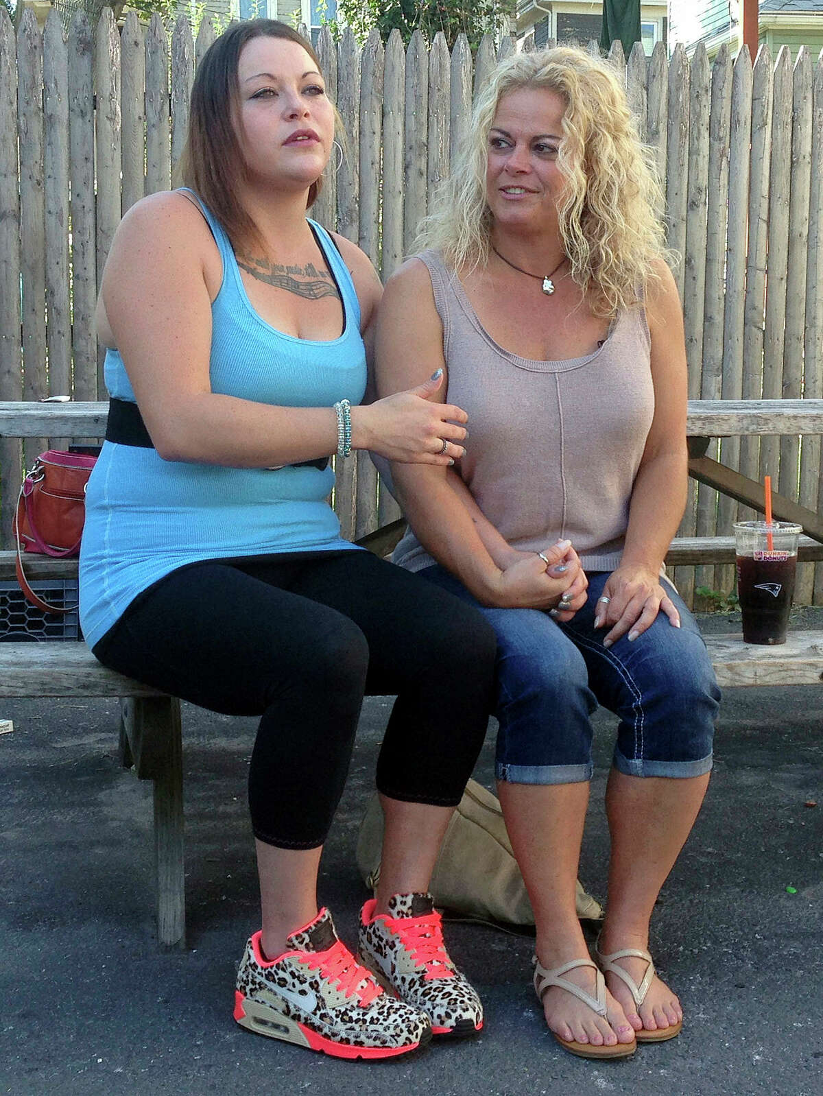 In this Sept. 18, 2015 photo, Kylee Moriarty, left, and her mother, Jackie Law, sit together outside the halfway house in Boston where Moriarty resided. This was their first meeting in person in more than a year. Moriarty is among more than 200 addicts taking advantage of a unique program offered by police in Gloucester, in which heroin addicts are fast-tracked into treatment rather than arrested.