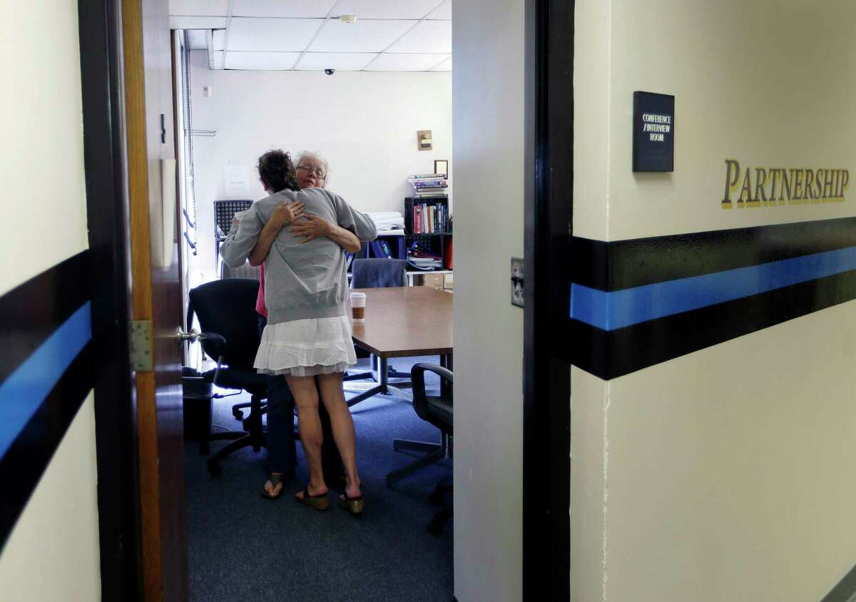 In this July 10, 2015 photo, volunteer Ruth Cote, facing, hugs Kylee Moriarty inside the police station in Gloucester, Mass., who had voluntarily come to the police for help kicking her heroin addiction.