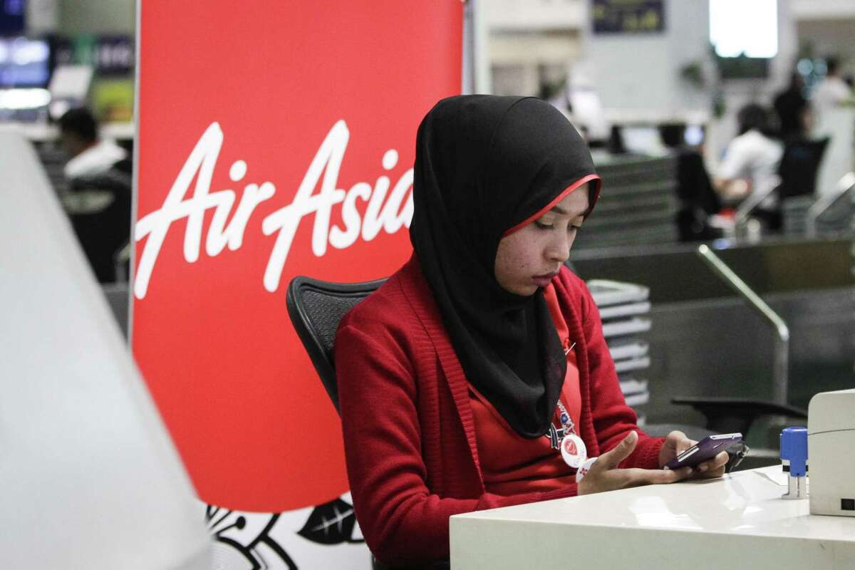 An AirAsia ground staff uses her smartphone at Kuala Lumpur International Airport 2 in Sepang, Malaysia on Feb. 8, 2015. AirAsia X said the flight heading from Malaysia to Saudi Arabia turned back shortly after takeoff due to a technical problem, circling for hours to burn fuel before landing safely in Kuala Lumpur.