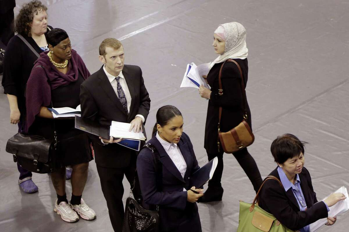In this Oct. 8, 2014 photo, job hunters line up for interviews at an employment fair sponsored by the New York State Department of Labor, in the Brooklyn borough of New York. Associated Press-GfK poll finds Americans' views of Obama have improved slightly in the past two months, as have opinions on the direction of the country and the strength of the economy.