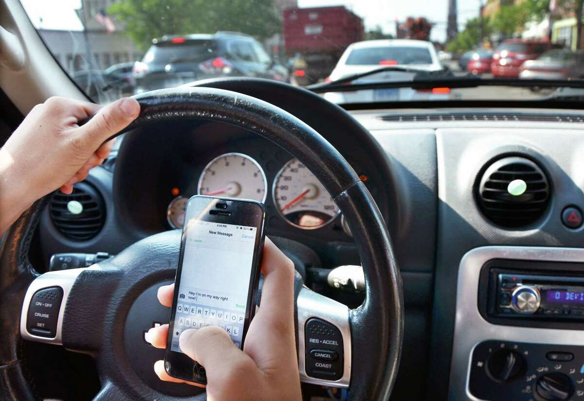 PHOTO ILLUSTRATION BY CATHERINE AVALONE — THE MIDDLETOWN PRESS Driving while texting.