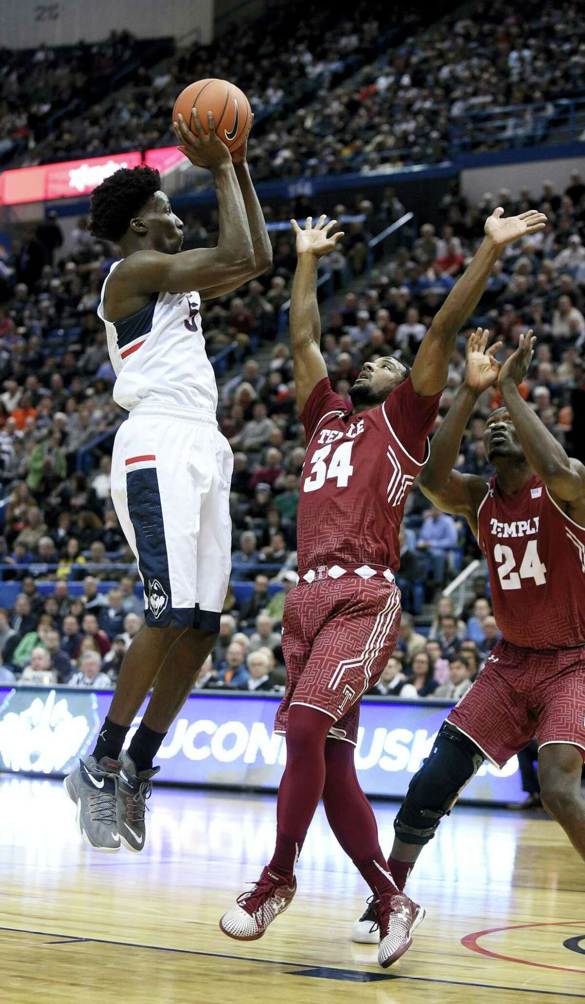 UConn's Daniel Hamilton, left, shoots over Temple's Devin Coleman during their game on Jan. 5.