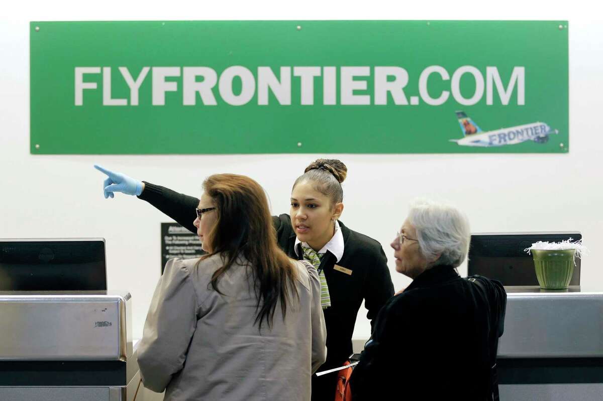 In this Oct. 15, 2014 photo, a Frontier Airlines employee directs passengers at Cleveland Hopkins International Airport in Cleveland.
