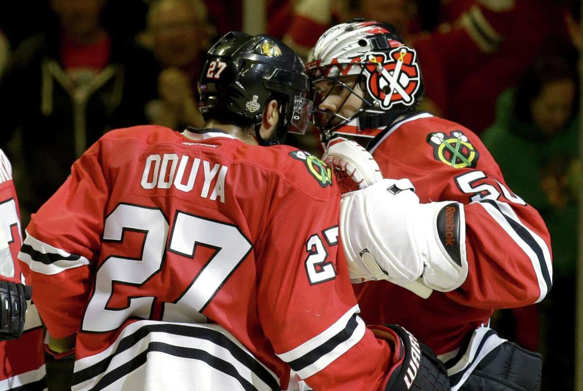 Goalie Corey Crawford, right, and teammate Johnny Oduya celebrate following the Blackhawks' 2-1 victory over the Tampa Bay Lightning in Game 4 of the Stanley Cup Finals on Wednesday in Chicago. The series is tied 2-2.