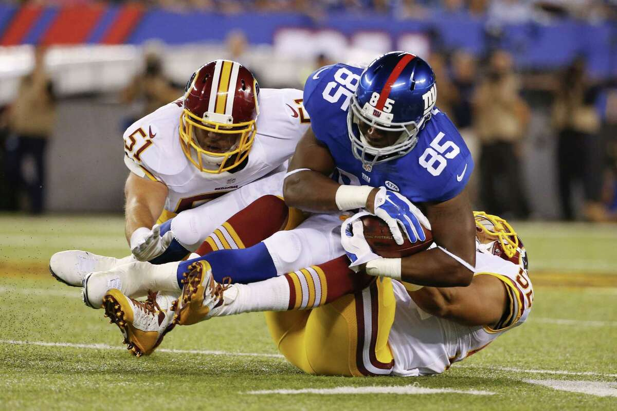 The Washington Redskins' Keenan Robinson (52) and Will Compton (51) tackle New York Giants tight end Daniel Fells during a Sept. 24 game in East Rutherford, N.J.