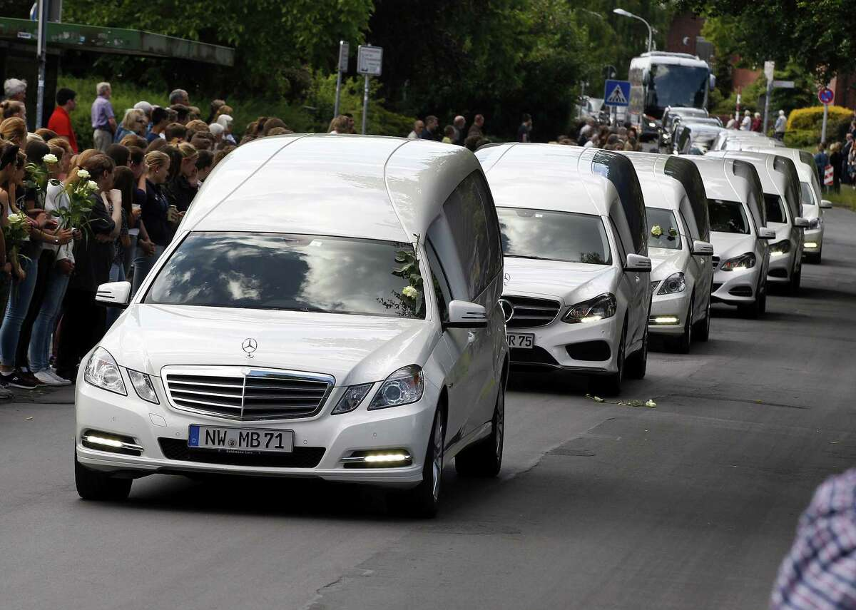White hearses carrying the remains of pupils killed in the Germanwings plane crash in France are about to pass by the Joseph-Koenig high school in Haltern, Germany, Wednesday, June 10, 2015. 150 people died in the plane crash on March 24. (AP Photo/Michael Probst)