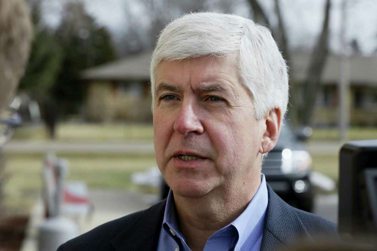 In this Friday, Feb. 5, 2016 photo, Michigan Gov. Rick Snyder is interviewed after visited a church that's distributing water and filters to its predominantly Latino parishioners in Flint, Mich. Snyder will propose spending $195 million more to address Flint's water crisis and another $165 million updating infrastructure across the state in response to lead contamination overwhelming the city.