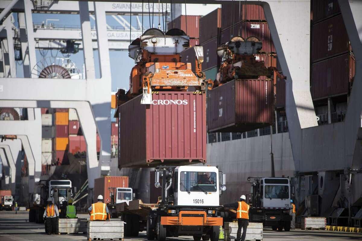 Ship to shore cranes load shipping containers onto jockey trucks from a cargo ship at the Port of Savannah in Savannah, Ga.
