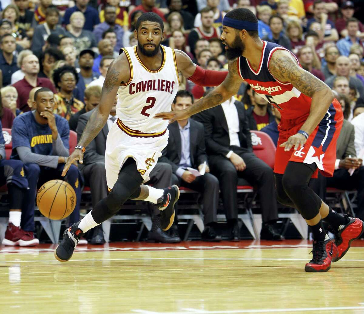 In this Oct. 18, 2016 photo, Cleveland Cavaliers' Kyrie Irving, left, drives past Washington Wizards' Markieff Morris during an NBA preseason basketball game in Columbus, Ohio. Cleveland's Big 3 — LeBron James, Kevin Love and Irving — have finally meshed after two turbulent, strange seasons when the trio of All-Stars were often disconnected. But whatever kept them from uniting seems to be resolved and they're determined to add to their legacy.