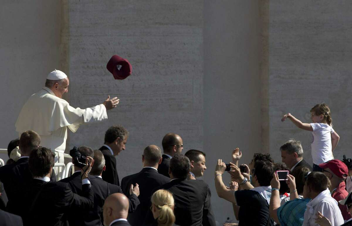A worshipper tosses a hat into the air as Pope Francis arrives for his weekly general audience in St. Peter's Square, at the Vatican, Wednesday, June 10, 2015.