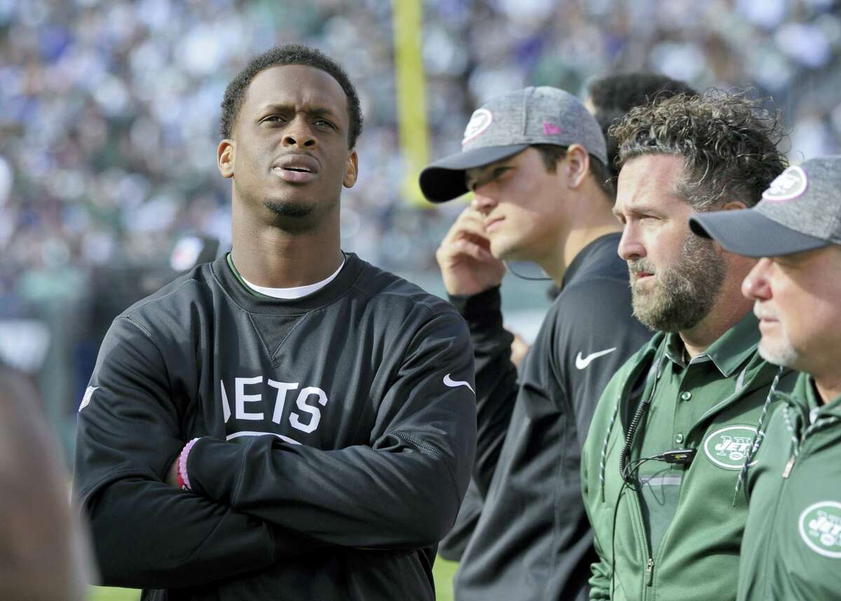 Jets quarterback Geno Smith, left, watches from the sidelines after leaving the game with a knee injury during the third quarter Sunday.