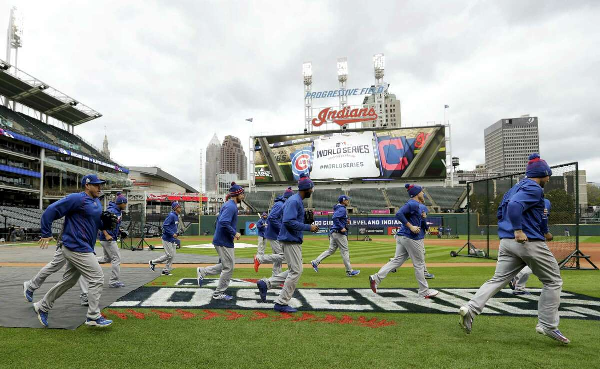Members of the Chicago Cubs warm up during a practice for the World Series Monday in Cleveland.