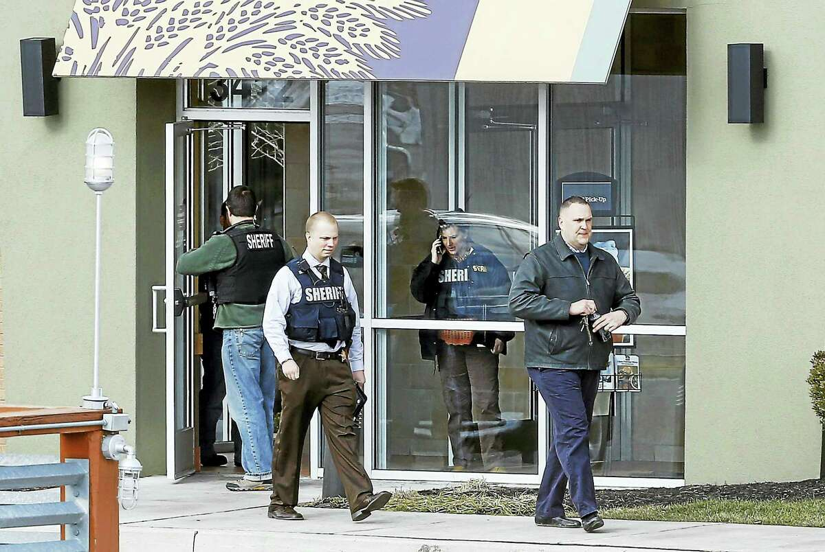 Investigators walk at the scene of a shooting at a shopping center in Abingdon, Md., Wednesday, Feb. 10, 2016. A man opened fire inside a shopping center restaurant during lunchtime.