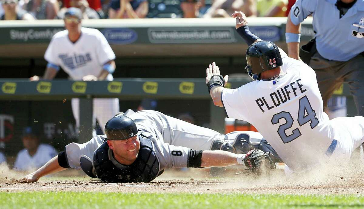 The Twins' Trevor Plouffe, right, is safe at home as he avoids the tag of Brian McCann in the sixth inning on Sunday.