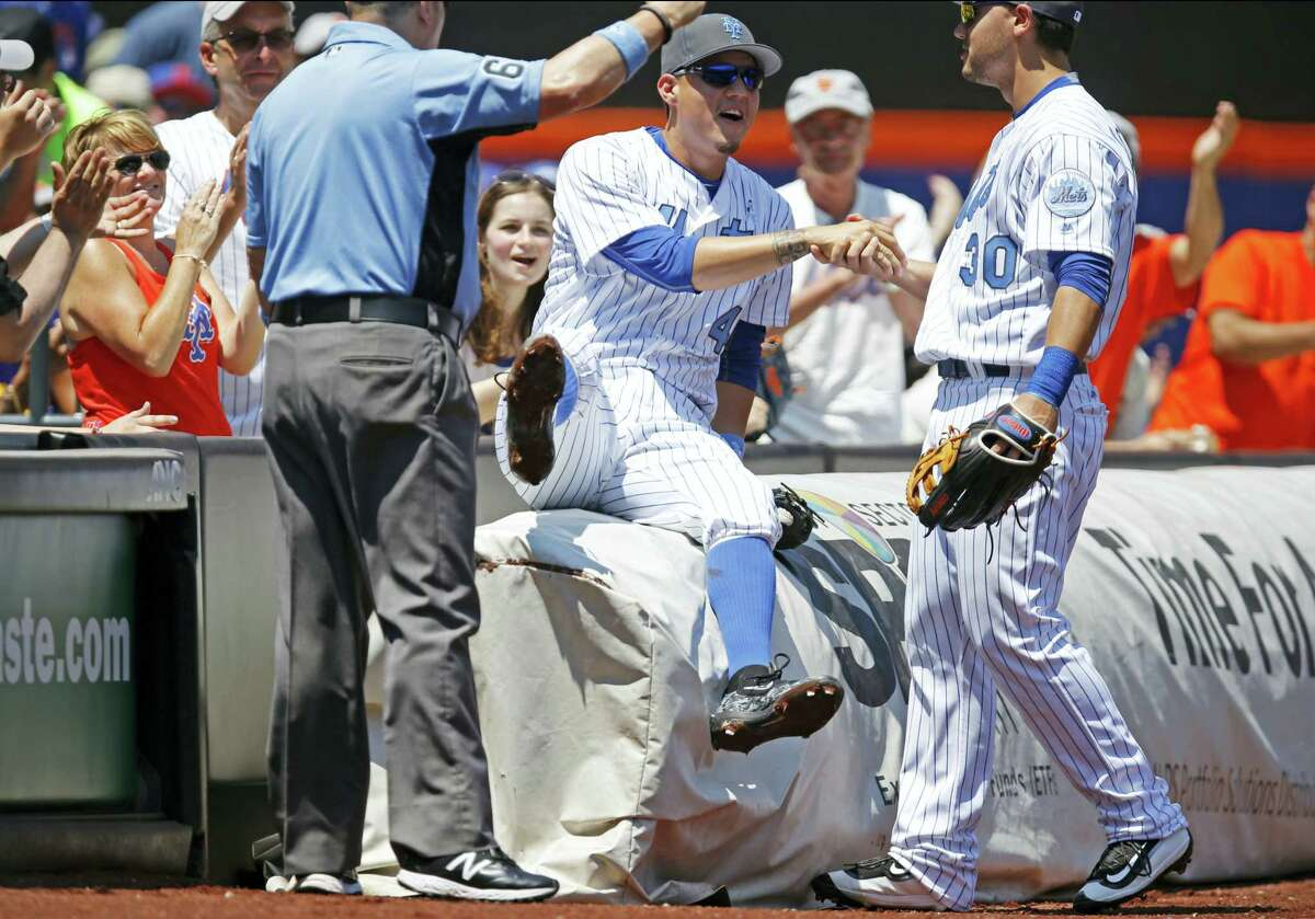Spectators applaud as Mets left fielder Michael Conforto (30) helps third baseman Wilmer Flores up after Flores caught a foul ball on Sunday.