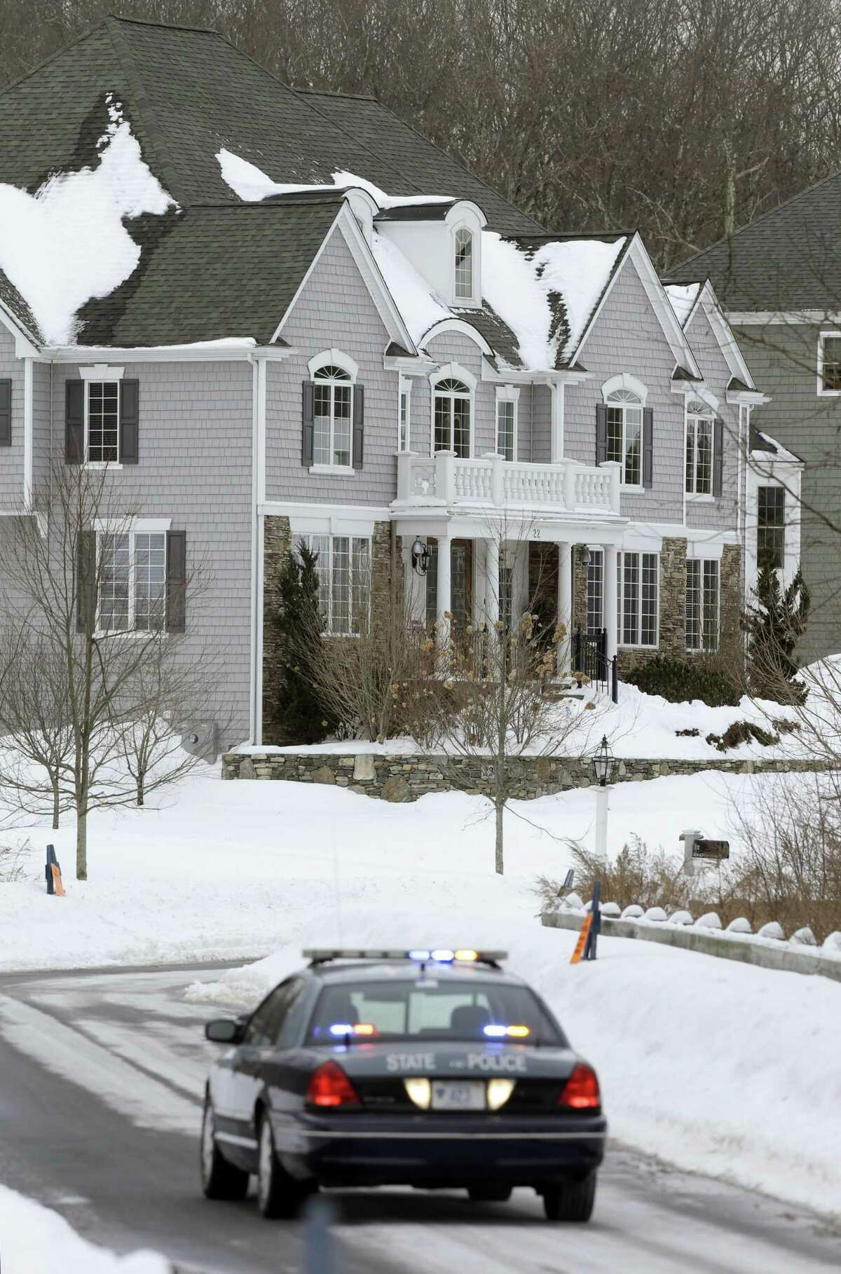 A State Police car sits on the street in front of the North Attleborough, Mass., home of former New England Patriots football player Aaron Hernandez, rear, during a site visit by the jury in his murder trial Friday. Hernandez is charged with killing semiprofessional football player Odin Lloyd in 2013. The jury toured several sites related to the case, including Hernandez's home, Lloyd's home, and the industrial park where Lloyd's body was found.