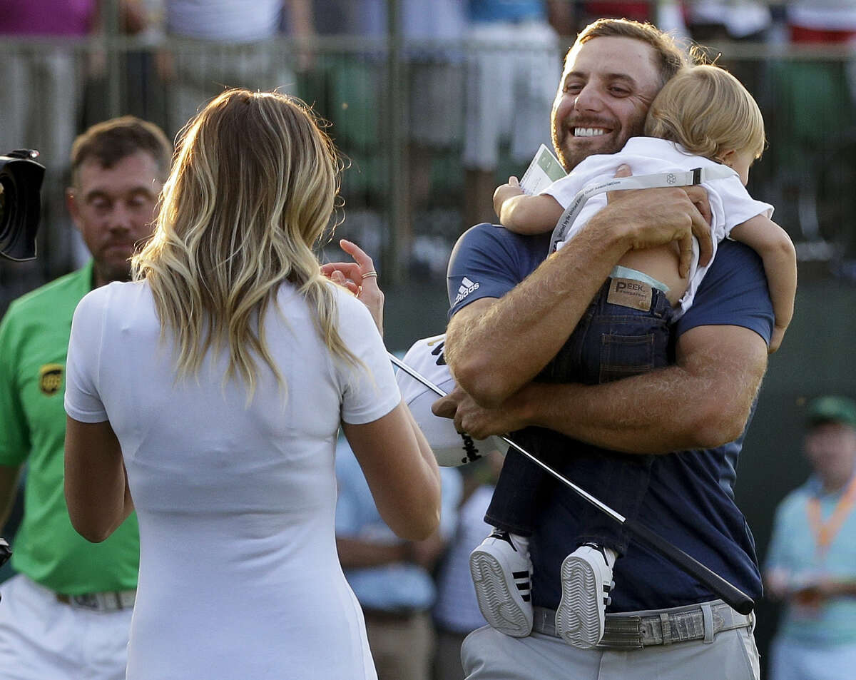 Dustin Johnson, right, greets his fiancé Paulina Gretzky as he holds their son Tatum Gretzky at the U.S. Open at Oakmont Country Club on Sunday.