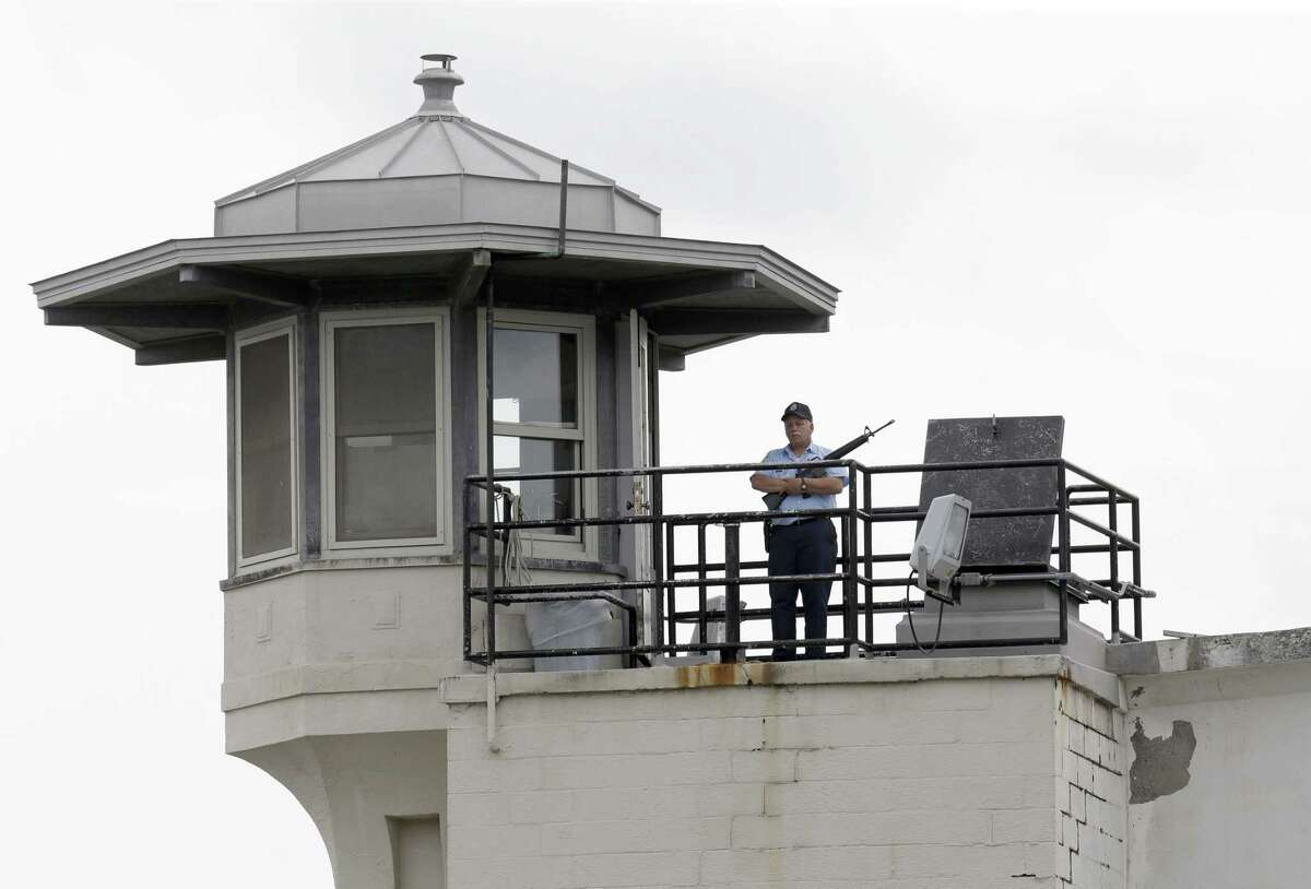 A prison employee stands guard on a tower at the Clinton Correctional Facility in Dannemora, N.Y., Wednesday, June 10, 2015. Police were resuming house-to-house searches near the maximum-security prison in northern New York where two killers escaped using power tools, authorities said Wednesday.
