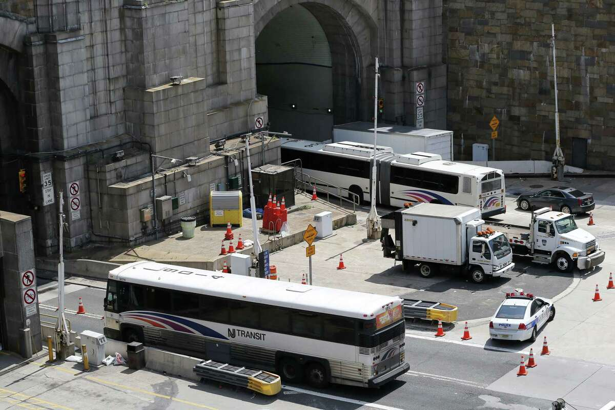 A New Jersey Transit bus, bottom, backs out of the center tube of the Lincoln Tunnel as another one is diverted into a different tube on the New Jersey side of the tunnel in Weehawken, N.J., Wednesday, June 10, 2015. A New Jersey transit bus rear-ended a private bus injuring at least 18 people at around 9:30 a.m. in the center tube on the New York side of the tunnel connecting it with New Jersey, according to a spokesman for the Port Authority of New York and New Jersey police. (AP Photo/Julio Cortez)
