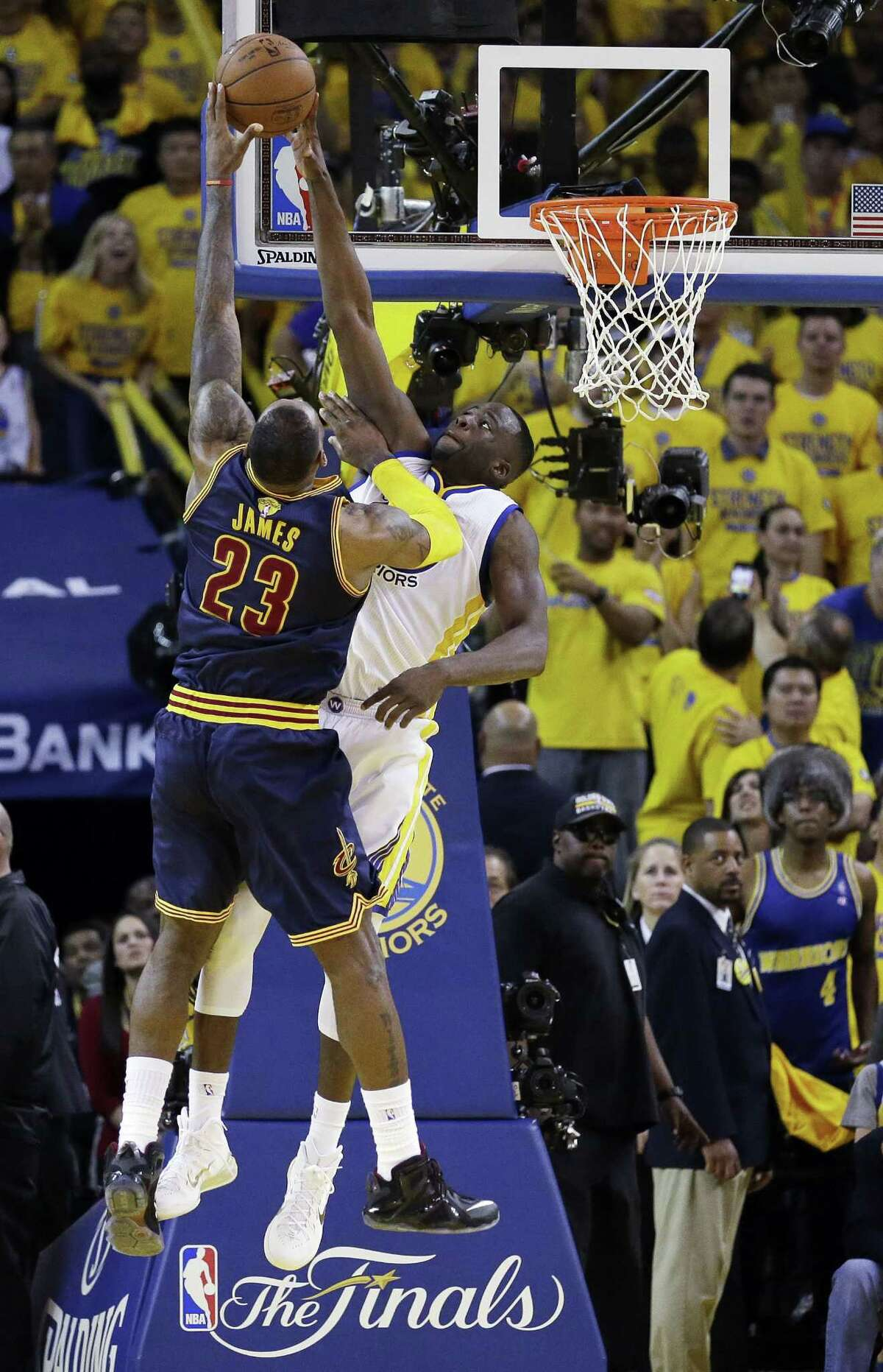 Golden State Warriors forward Draymond Green, right, blocks a shot attempt by Cleveland Cavaliers forward LeBron James during the overtime period of Game 2 of basketball's NBA Finals in Oakland, Calif. on June 7, 2015. The Cavaliers won 95-93 in overtime.