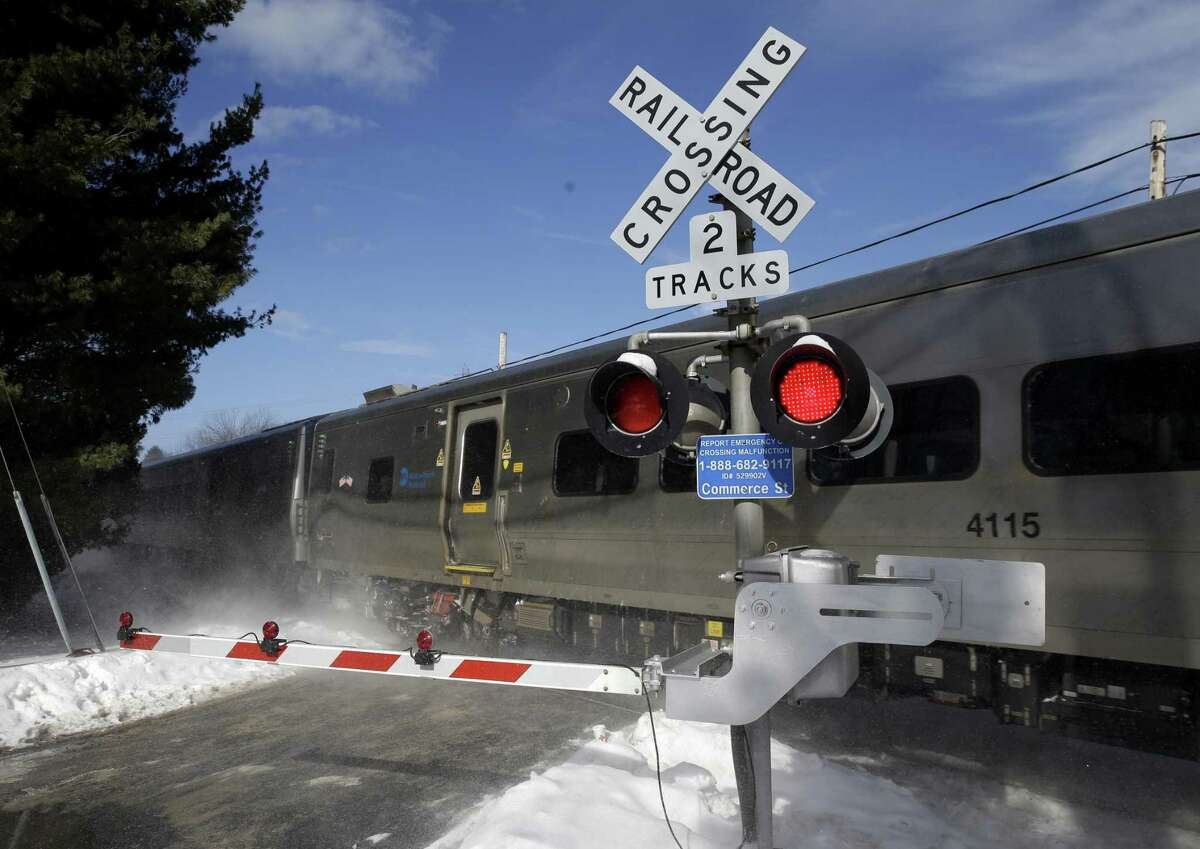A train passes through the intersection where an SUV was struck by a Metro-North Railroad train in Valhalla, N.Y., Thursday, Feb. 5, 2015. An investigation into what caused a fiery crash that killed a motorist and five rail riders is focusing on how a mother of three described by friends as safety conscious ended up between two crossing gates in her SUV as a commuter train barreled toward her. (AP Photo/Seth Wenig)