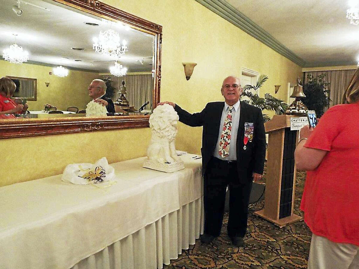 Contributed photosOutgoing Torrington Lions Club President Phil Dzurnak shows a gift from the club: a large white lion that lights up at night.