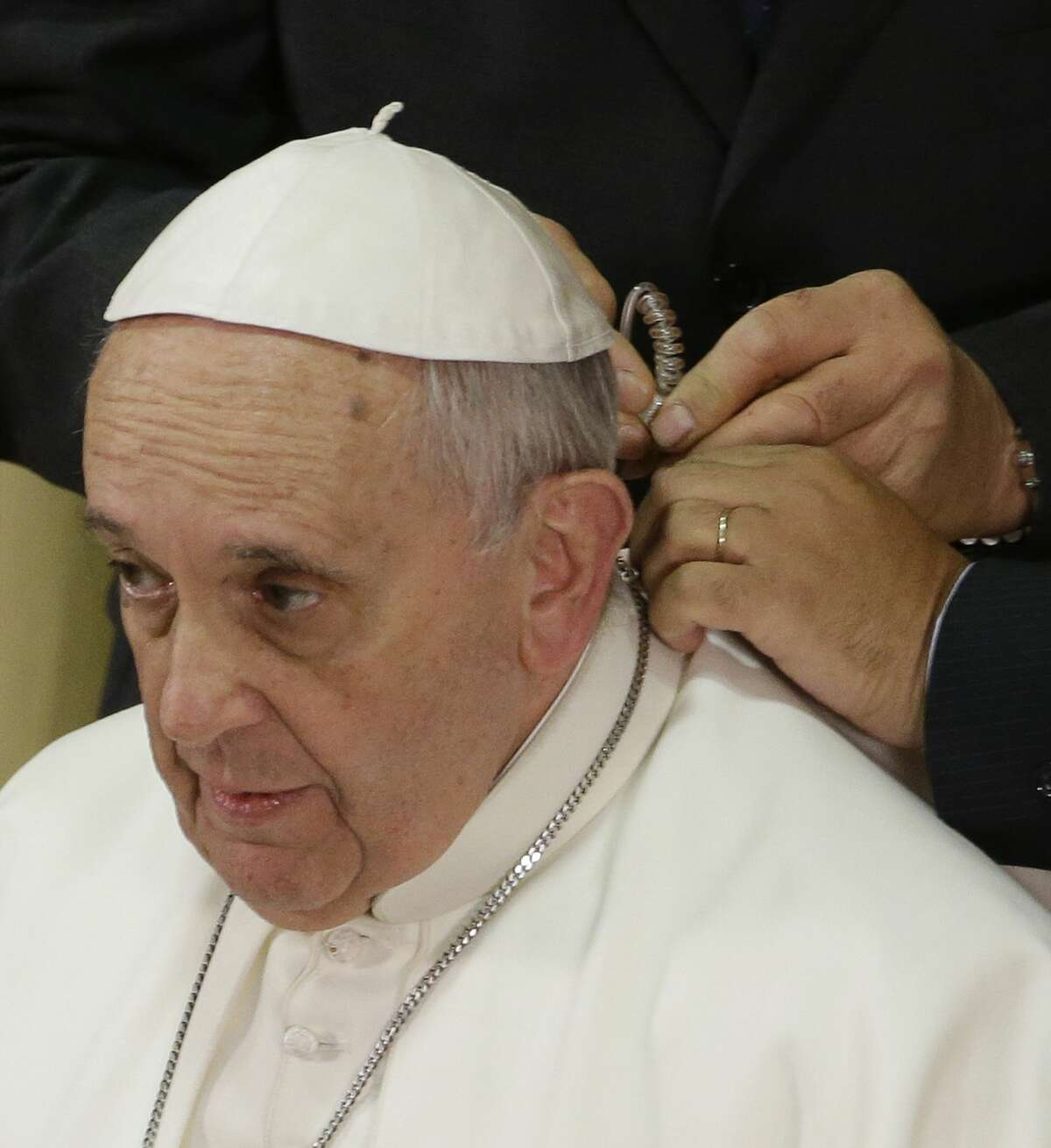 Pope Francis has an headset applied by two Vatican radio technicians prior to giving his his speech in the Synod hall on the occasion of the closing ceremony of the IV Scholas Occurrentes World Educational Congress, at the Vatican, Thursday, Feb. 5, 2015. (AP Photo/Gregorio Borgia)