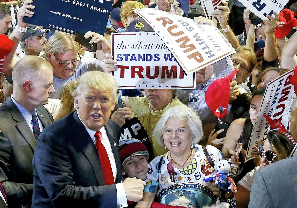 Republican presidential candidate Donald Trump, left, shouts to Secret Service agents that supporter Diana Brest, right, had been waiting in line since 2 a.m. to see the candidate speak at a rally on June 18, 2016 in Phoenix.