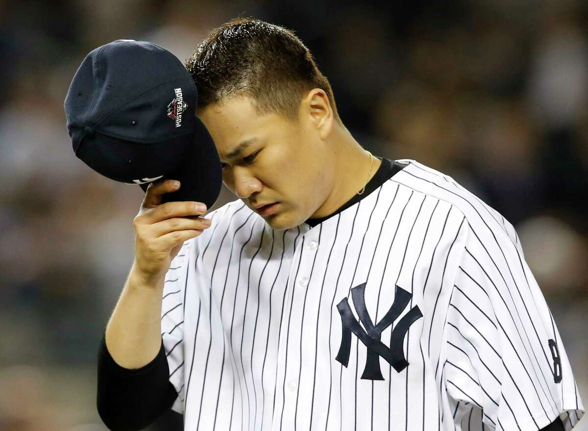 New York Yankees starting pitcher Masahiro Tanaka removes his cap as he leaves the mound in the fifth inning of the American League wild card baseball game against the Houston Astros at Yankee Stadium in New York, Tuesday, Oct. 6, 2015. (AP Photo/Kathy Willens)