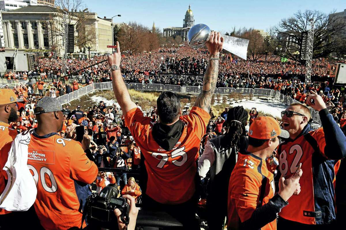 Broncos defensive end Derek Wolfe (95) holds the Lombardi Trophy over his head as he looks over a massive crowd during the Broncos Super Bowl rally on Tuesday.