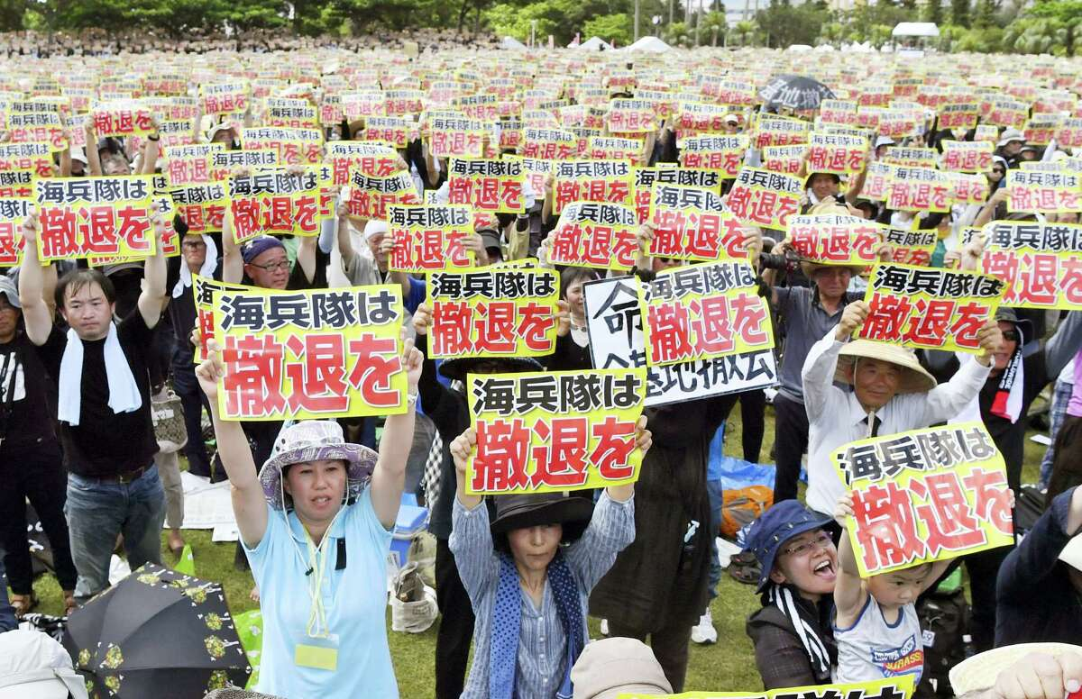 """Protesters hold placards that read: """"U.S. Marines, withdraw"""" during a protest rally against the presence of U.S. military bases on the southwestern island of Okinawa in Naha, Okinawa on June 19, 2016 as many of them wearing black to mourn the rape and killing of a local woman in which a former U.S. Marine is a suspect."""