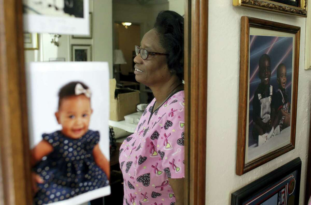 In this photo taken Oct. 18, 2016, Gwen Strowbridge, 71, poses for a photograph among photos of her grandchildren wearing her work uniform at her home in Deerfield Beach, Fla. Strowbridge works six days a week caring for a 100-year-old woman. She has worked all her life and plans to work until she can't physically work anymore.