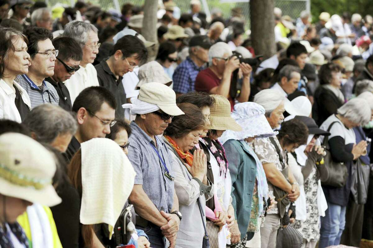 Protesters observe a moment of silence for a local Japanese woman who was raped and killed by a former U.S. Marine, during a protest rally against the presence of U.S. military bases on the southwestern island of Okinawa in Naha, Okinawa on June 19, 2016.