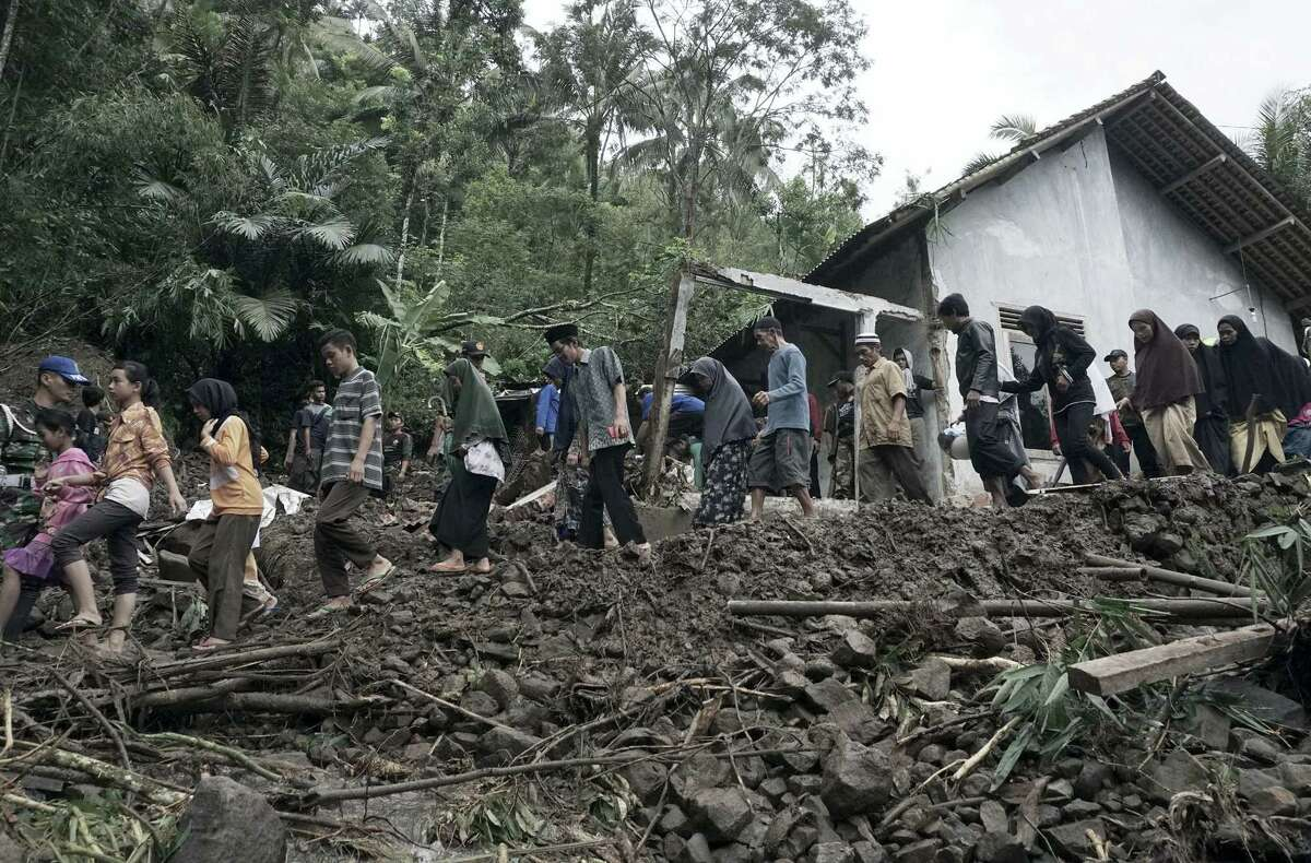 Villagers walk through the area affected by landslides in Banjarnegara, Central Java, Indonesia on June 19, 2016. An Indonesian official said dozens of people have been killed by flooding and landslides in central Java and many others remain missing.